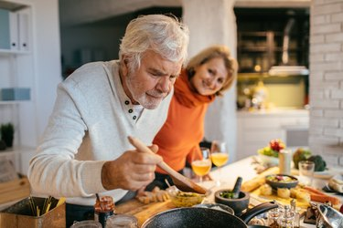 Older couple preparing meal in kitchen with nutrients for longevity