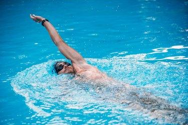 man swimming backstroke in a swimming pool