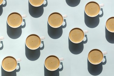 pattern made of mugs of coffee on light blue background