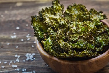 Homemade green kale chips baked with balsamic vinegar in bowl on rustic wooden background