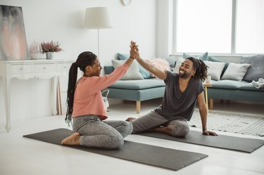 man and women exercising in living room, giving a high-five as they get in shape after being sedentary