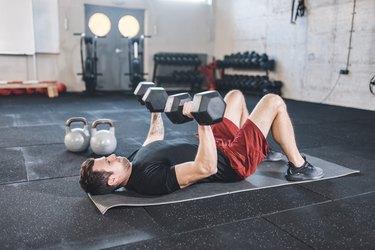 man doing dumbbell chest press exercise on a black yoga mat
