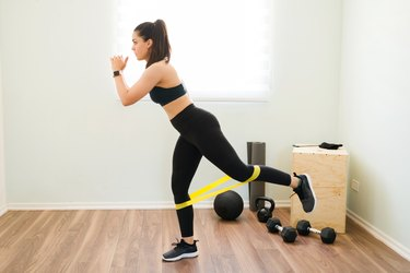 Athletic woman doing a resistance band leg workout at home