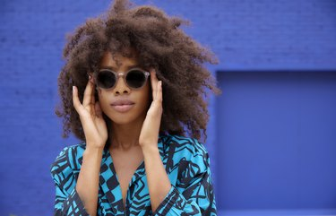 Young Black woman wearing sunglasses in front of blue wall