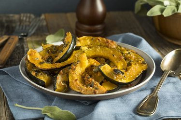 Magnesium- and potassium-rich baked and sliced acorn squash on a blue napkin with a spoon