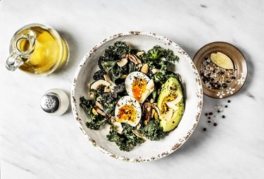 Bowl of kale salad with boiled eggs and avocado on marble white background
