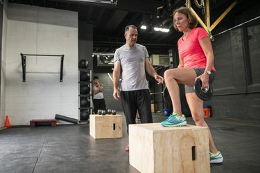 mature woman learning how to do a step-up without mistakes in the gym