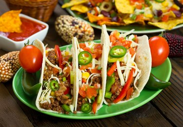 Beef tacos on green plate with toppings