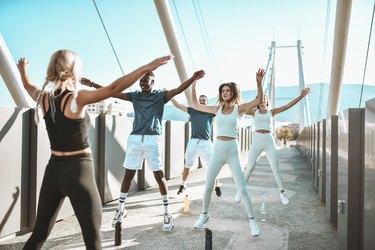 Jumping Jacks Exercise By Multiethnic Fitness Team Outside On Bridge