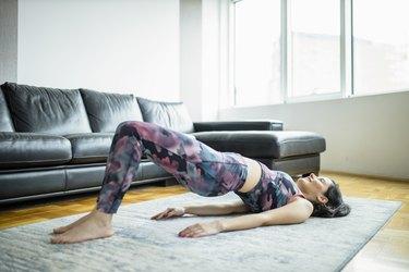 Woman practicing yoga, doing Glute Bridge exercise, dvi pada pithasana at home