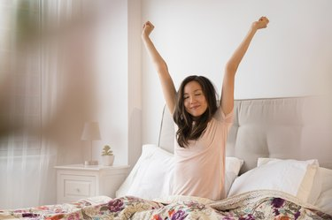 woman stretching in bed, as a natural remedy for insomnia