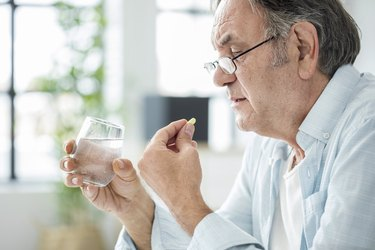 Older man taking a pill with water glass