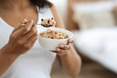 Healthy Meal Concept. Unrecognizable black woman eating oatmeal with fruits for breakfast