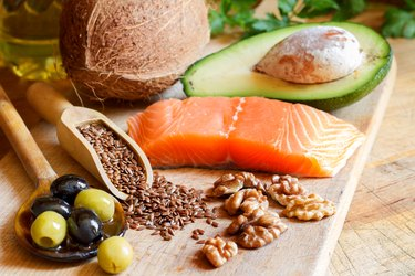 Foods high in healthy fats, including avocado, salmon, olives, nuts and seeds, on wooden board