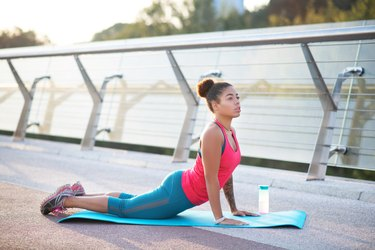 African American woman wearing blue leggings and orange shirt doing yoga outside