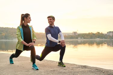 Young man and woman stretching before running