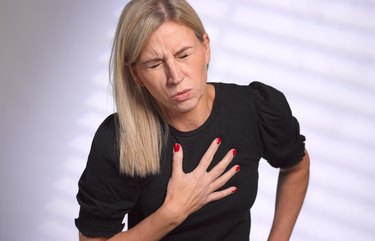 Adult woman clutching heart in pain