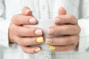 Manicured hands holding a cup of coffee or tea