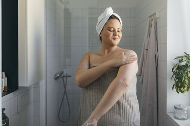 a woman applying lotion after a shower, as a natural remedy for sunburns