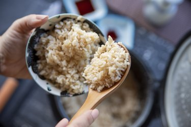 hands scooping gluten-free steamed rice into bowl