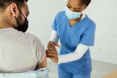 Female nurse administers COVID vaccine to male patient