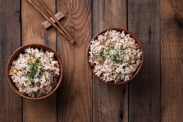 fried rice with vegetable and grains in bowl on wooden table
