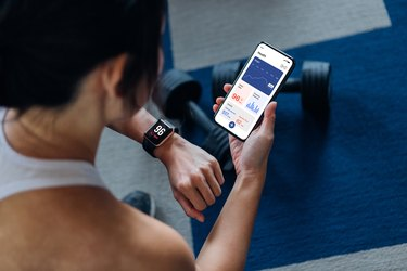 Over the shoulder view of young woman using exercise an tracking app to track her strength sessions, wondering how long should a weightlifting workout last to be effective