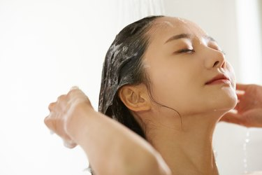 Young Asian woman shampooing in the bathroom