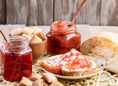 Toasts and jar with strawberry and apple jams, square snacks on yellow knitted napkin on rustic wooden table.