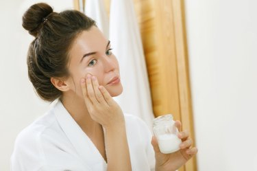 Woman applying coconut oil on her face
