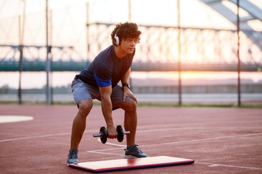 man wearing headphones and doing a dumbbell workout on a track