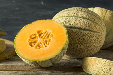 whole and cut vitamin C-rich cantaloupe on wooden table