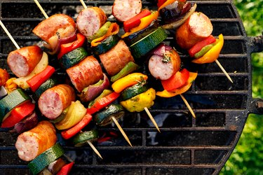 Grilled skewers of meat, sausages and various vegetables on a grill plate, outdoors, top view.