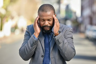 Man outside pressing his temples because he has a cold weather headache