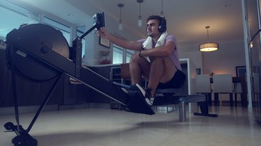 man adjusting settings on a rowing machine at home