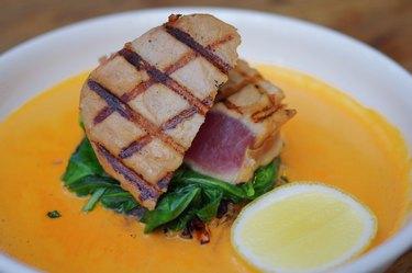 Grilled tuna fish steak with vegetable, slice of lemon and orange sauce