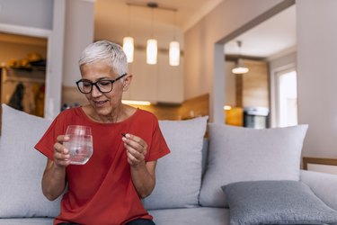 older woman holding a multivitamin in her hand