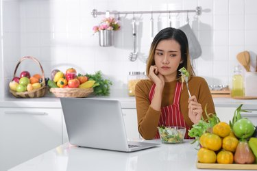 Displeased young Asian woman eating salad . unsatisfied woman eating vegetarian food  while using laptop at table in kitchen . healthy food concept .