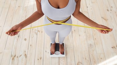 Above view of African American lady measuring her waist with tape, standing on scales indoors, closeup