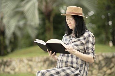 A pregnant woman sits in a park and reads her journal