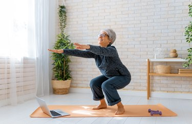 senior woman doing squats on an orange yoga mat at home