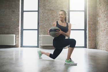 Woman performing rotating lunge with medicine ball.