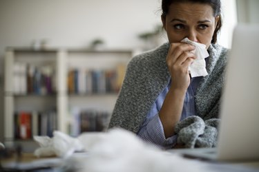 woman working at her desk and holding a tissue to stop her nosebleed