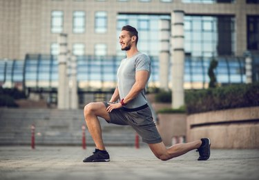 Happy male athlete exercising lunges on the city street.