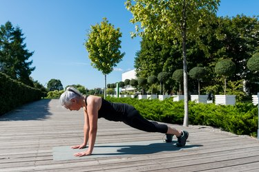 Strong mature woman holds plank position