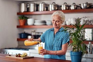 Older woman pouring juice for breakfast for longevity