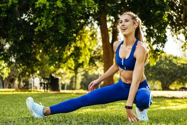 woman in blue leggings and sports bra doing a warm-up stretch before exercise in the park