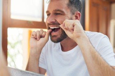 man in the bathroom flossing before brushing his teeth