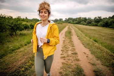 a woman in a yellow jacket running outside in a field