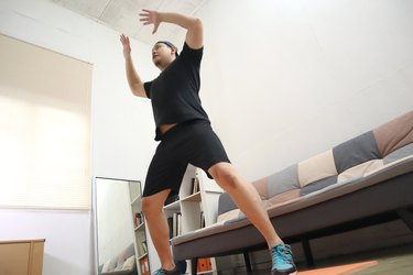 Asian male doing exercise at home to stay healthy on new normal lifestyle, indoor home workout, body weight cardio circuit training
